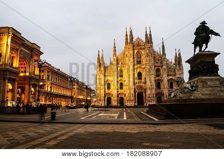 Milan, Italy. Cathedral of Milan, Italy at sunrise - famous landmark in the city. Motion blurred people, illuminated Gallery entrance, cloudy sky in the morning