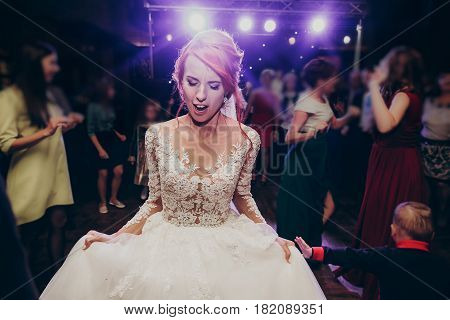 Stylish Happy Bride Dancing At Wedding Reception. Gorgeous Wedding Couple Having Fun And Partying In