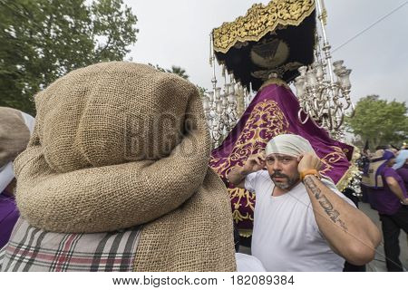 Linares, SPAIN - April 14: Group of costaleros name given to those who carry thrones, takes a rest during a religious procession in the streets of Linares, procession of holy week, Andalucia, Spain