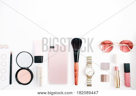 Beauty blog fashion concept. Female pink styled accessories: cell phone watches sunglasses cosmetics on white background. Flat lay top view trendy feminine background.