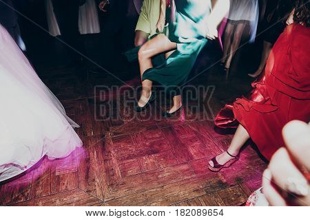 happy dancing at wedding reception. gorgeous guests and wedding couple having fun and partying in restaurant in light show. emotional moment. space for text. legs close up