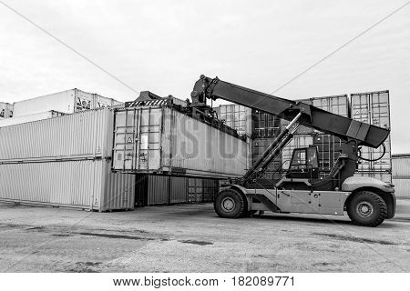 Maritime transportation industry. Mobile stacker handler in action at a container terminal.