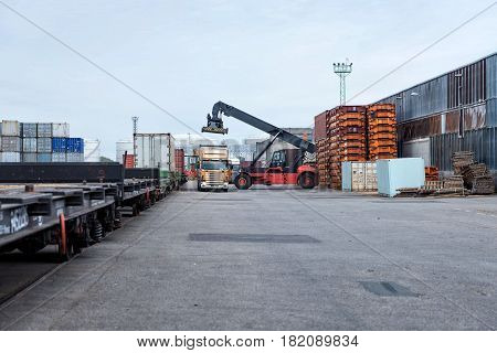 Maritime transportation industry. Container stacker unloads trucks.