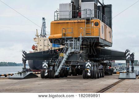 Maritime transportation industry. A giant crane on wheels at the port transshipped vessels.