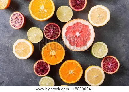 Different citrus fruit on gray concrete table. Whole and sliced fruit. Food background. Healthy eating and diet. Citrus fruits. Оrange lemon grapefruit mandarin lime. Copyspace
