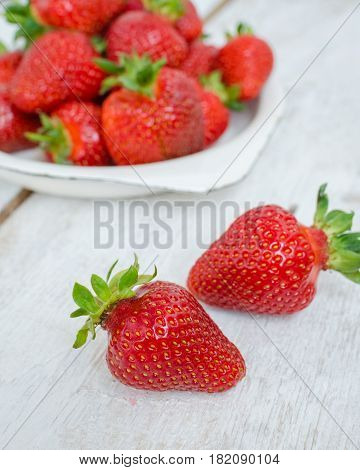 Red berry strawberry in white metal plate on white rustic wooden background. Background from freshly harvested strawberries. Strawberry background. Selective focus. Shallow depth of field. Vertical.