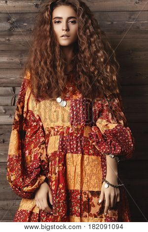 Brunette girl with long and shiny wavy hair . Beautiful model with curly hairstyle. Boho indian style