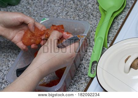 Preparation Of Tomato Soup. A Woman Cleanses Tomatoes From The Peel.