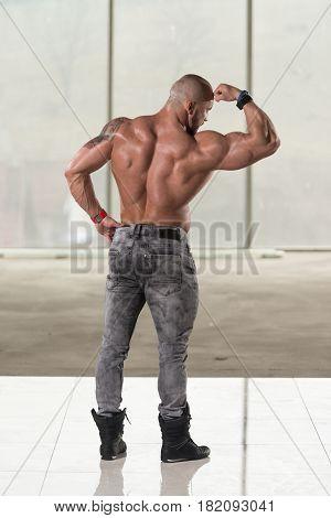 Muscular Man Flexing Back Muscles Pose
