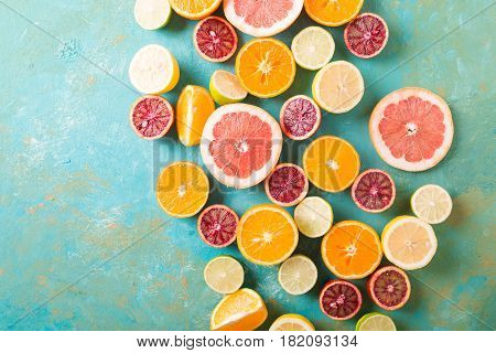 Citrus fruits on turquoise abstract background. Оrange lemon grapefruit mandarin lime. Mixed festive colorful tropical and citrus fruit sliced. Healthy eating photo concept. Copyspace