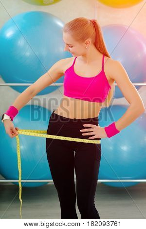 The Woman Is Standing And Measuring Her Waist With A Tape-line