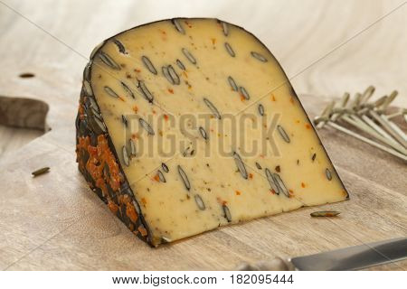 Dutch cheese with pumpkin seeds and carrot on a cutting board