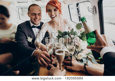 Stylish Happy Bride And Groom Toasting With Glasses Of Champagne And Having Fun With Bridesmaids And