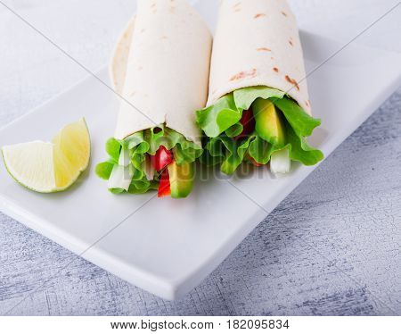 Vegetable wrap sandwiches with greenery and tomatoes