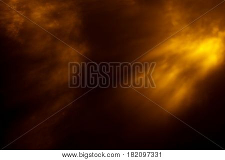 Abstract background with blurred golden light on black