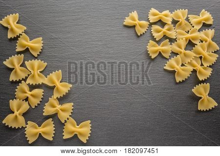 Farfalle noodles at slate black board with copy space from top view
