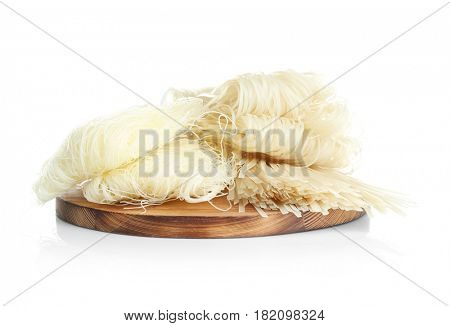 Wooden board with rice noodles on white background