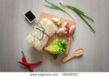Wooden board with rice noodles and products on table