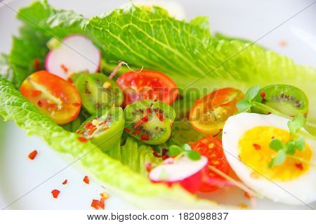 Salad of romaine leaves boiled egg cherry tomatoes radishes and baby kiwi fruit with red pepper flakes