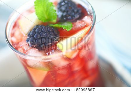 Closeup of icy wine cocktail with fresh apple and blackberries