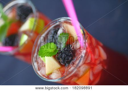 Two icy wine drinks with blackberries apple pieces straws and copy space