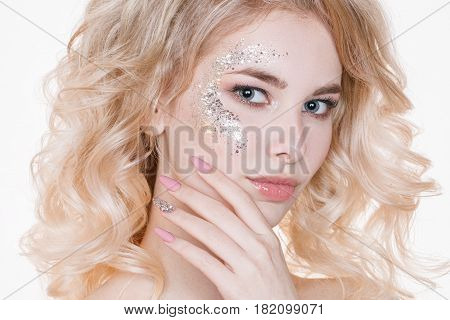 Beauty women portrait of young curly blond woman with pastel manicure and perfect art make-up with glitter. Isolated. Studio