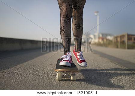 Young skater girl skateboarding at the street