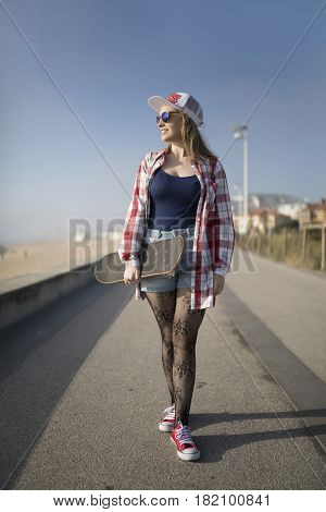 Young skater woman walking and holding a skateboard