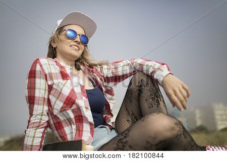Portrait of a young skater girl posing with a skateboard