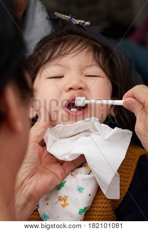 Asian baby toddler girl is brushing her white teeth before going to sleep.