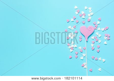 pink heartshaped sweets and sugar candies on blue desk background top view mock-up