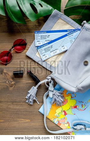 traveller set with map, glasses, bag and tickets in vacation design on wooden table background top view