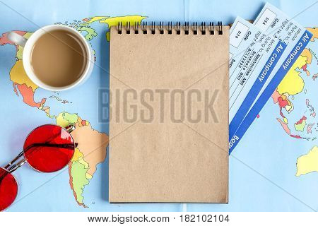 tourist stuff with notebook, coffee and flight tickets on map background top view mockup