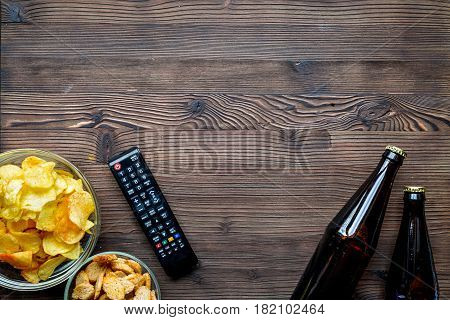 TV remote control, snacks, beer on wooden desk background top view space for text