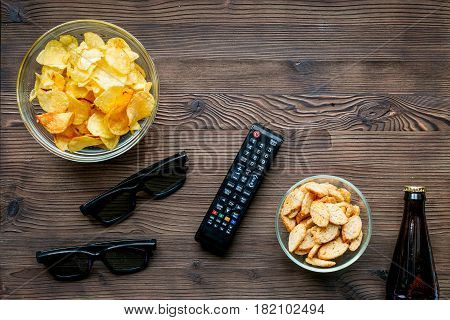 watching movies set with chips, beer and remote control on wooden background top view mock up