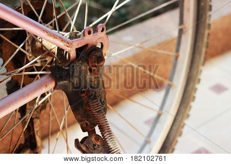 The old pink bicycle is rusty, dense brown island