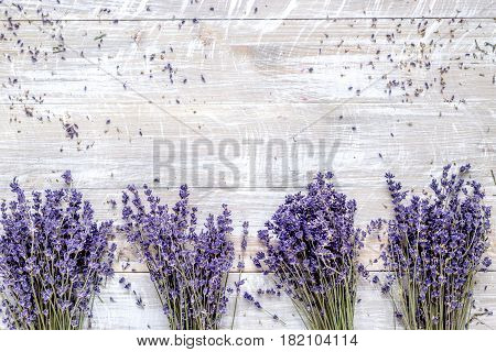 Bunch of dry lavender flowers on rustic desk background top view mock up