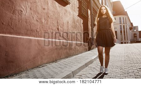 Beautiful Brunette Young Woman Wearing Dress And Walking On The Street. Flare For Text And Design. L