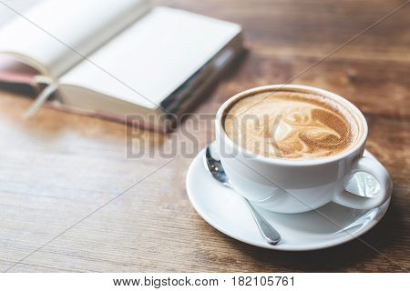 A cup of coffee with open notebook on wooden table.