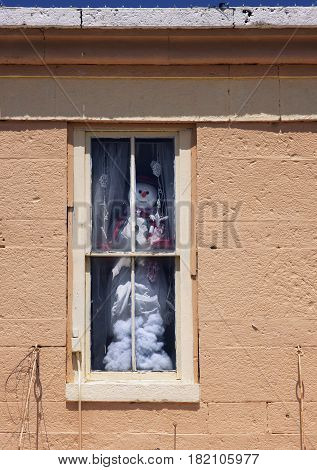 A snow man peers from a window in a building on the square in Lampasas, Texas