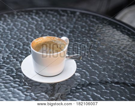 Empty white cup of coffee on glass table morning