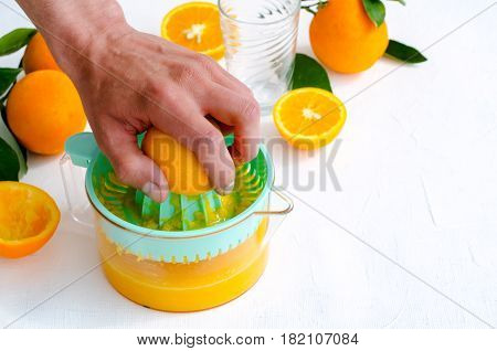 Freshly squeezed orange juice by men's hand, in turquoise juicer on white background, horizontal, copy space
