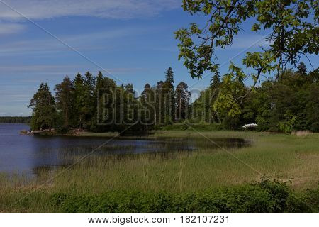 VYBORG, LENINGRAD OBLAST, RUSSIA - JUNE 6, 2015: People resting in the landscaped English park Mon Repos. Former manor of the Barons von Nikolai, now it is one of main tourist attraction in the town