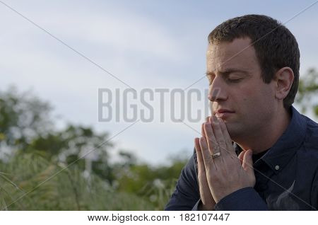 Close up of married man praying outdoors with blue sky and green plants in the background.