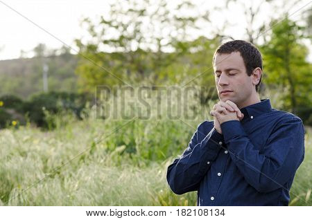 Married man praying outdoors in a grassy field with hands clasped up to his chin.