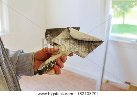 Painting worker puttied wall using a paint spatula hand. Closeup photo