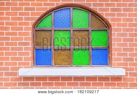 Window decorated with stained glass on the brick wall.