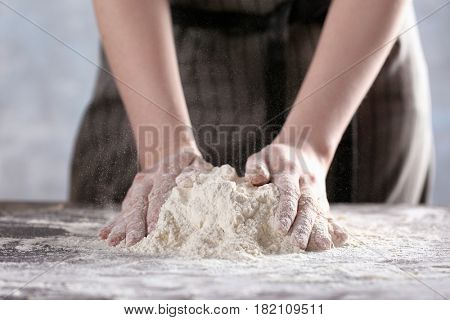 Woman making dough for ravioli on table