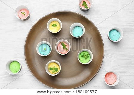 Tray with ice cream collection in paper cups on wooden background