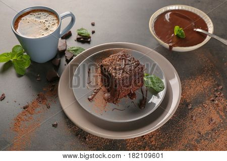 Plates with delicious cocoa brownie on table